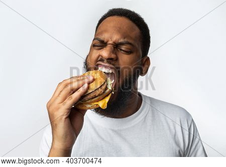 African Man Biting Burger Enjoying Unhealthy Tasty Junk Food Standing In Studio Over White Backgroun
