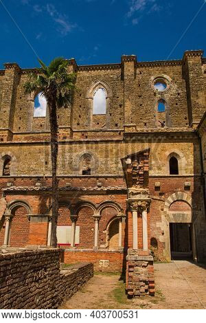 Chiusdino, Italy - 7th September 2020. A side view of the roofless San Galgano Abbey in Siena Province, Tuscany, showing lancet or pointed arch windows at the top and arch or radius arches at the bottom. Gothic 13th-century Abbey