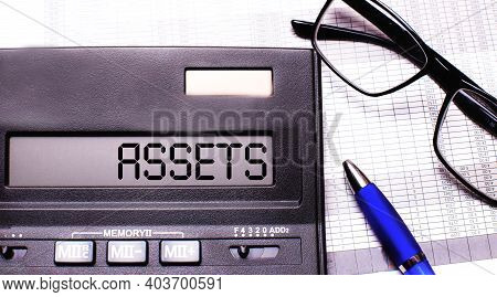 The Word Assets Is Written In The Calculator Near Black-framed Glasses And A Blue Pen.