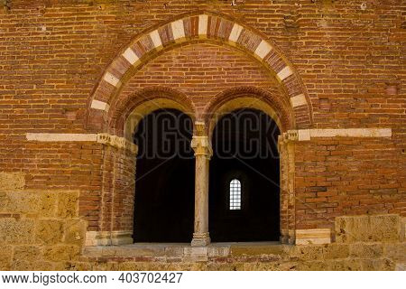 Chiusdino, Italy - 7th September 2020. A double arched or radius window in the remains of the roofless San Galgano Abbey in Siena Province, Tuscany. Gothic 13th-century Abbey