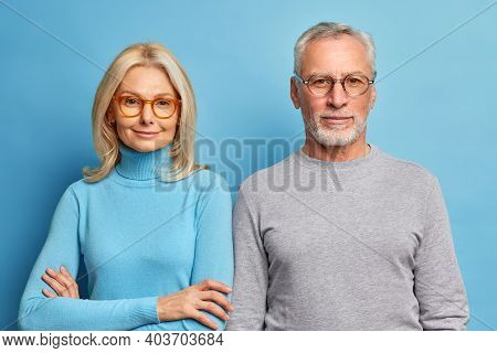 Portrait Of Mature Woman And Man Stand Next To Each Other In Casual Clothes Against Blue Background