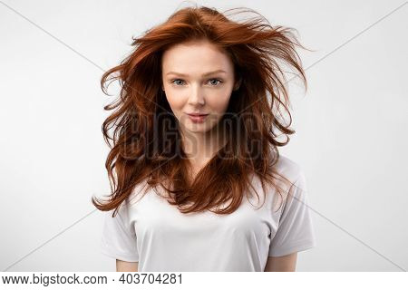 Beauty Portrait Of Red-haired Young Woman With Loose Hair Style Posing Smiling To Camera Standing Ov