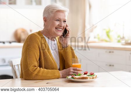 Cheerful Grandmother Having Phone Call While Eating At Home, Sitting On Cozy Kitchen And Looking At