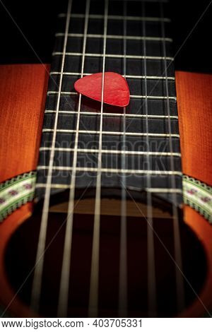 Extreme Closeup Of A Red Guitar Pick (plectrum) Between The Strings Of The Fretboard Of An Old Acous