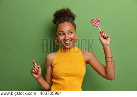 Positive Beautiful Curly Haired Woman With Toothy Smile Holds Lollipop Has Fun And Dances Carefree W