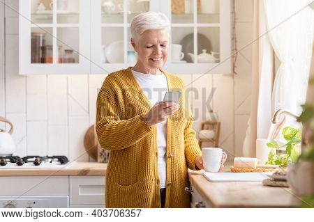 Smiling Old Lady Modern Grandmother Using Mobile Phone And Drinking Coffee, Standing Alone At Kitche