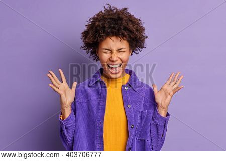 Overjoyed Afro American Girl Exclaims Loudly Keeps Hands Raised Feels Excited And Very Happy To Hear