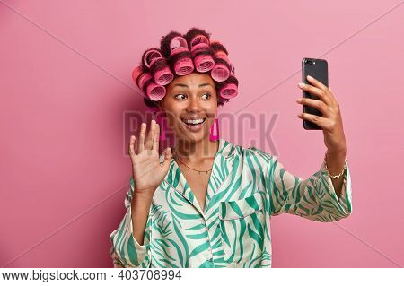 Positive Dark Skinned Woman With Hair Rollers On Head Smiles Broadly Waves Palm At Smartphone Camera