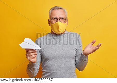 Puzzled Hesitant Grey Haired Man Raises Palm And Feels Confused Wears Disposable Mask To Protect Fro