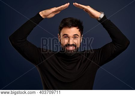 Waist-up Portrait Handsome Man With Bristle, Wear Trendy Sweater Raising Hands Above Head As Making