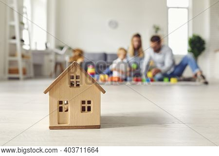 Close Up Of A Small Wooden House On The Background Of A Young Family Who Dreams Of Their Home.