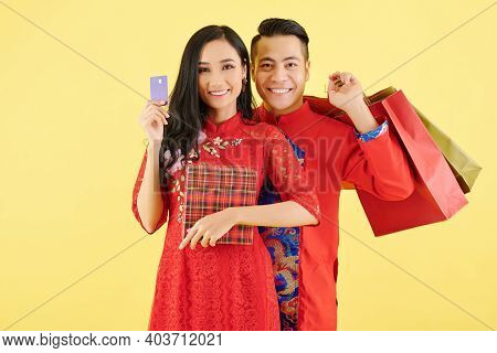 Portrait Of Smiling Young Asian Couple With Presents They Prepared For Lunar New Year Celebration