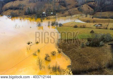 Aerial drone view of water pollution of a copper mine exploitation. Chemical residuals flooded natural environment, ecological bomb. Geamana, Rosia Montana, Romania