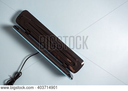 Close-up Of An Open Vacuum Packer Isolated On A Bright Blue Background. A Machine For Preserving The