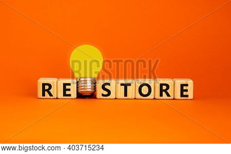 Restore Symbol. Wooden Cubes With The Word 'restore'. Yellow Light Bulb. Beautiful Orange Background