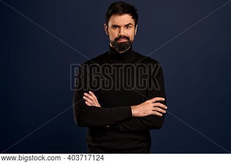 Portrait Of Serious Displeased Male Stands Crossed Hands Against Blue Background, Scowl Face In Diss