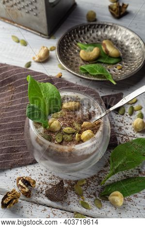 Chia Pudding With Cocoa, Spinach And Nuts In Almond Milk