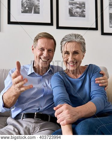 Happy Older Couple Greeting Family Making Online Video Call Talking To Web Cam. Middle Aged Old Gran