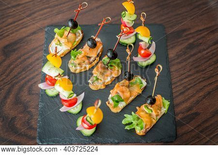 Fish And Meat Snacks On A Festive Table With Spices And Sauces. Meat, Bread And Snacks