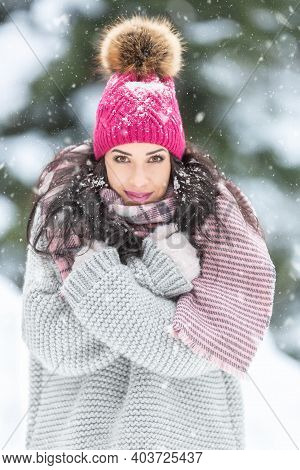Winter Fashion Outdoors Captured On A Female Model Wearing Ping Pom Pom Hat, Grey Sweater And Pink K