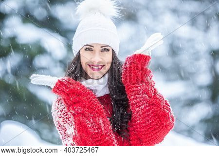 Young Woman Smiles In The Snow-covered Forest Wearing Fashion Outwear Such As Red Sweater, And White