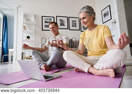 Happy Old Middle Aged Senior 50s Couple Learning To Meditate At Home Watching Live Online Tv Yoga Cl
