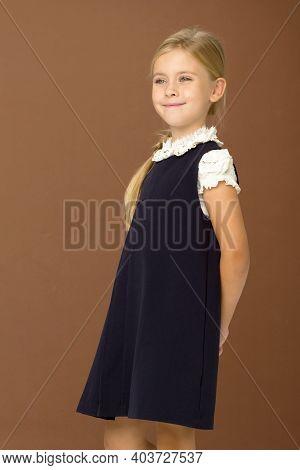 Cute Blonde Girl In School Uniform. Lovely Schoolgirl Wearing In White Blouse And Blue Dress Posing