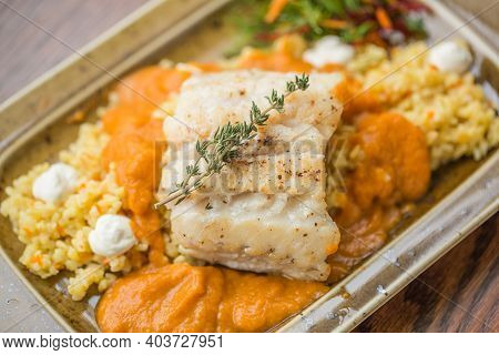 Fish In Batter With Fresh Farm Vegetables. Fillet Of Tilapia Fish In Batter. Baked Fish Garnished Wi