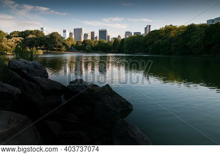 View Over New York City From Central Park And The Lake, Usa. Summer And Blue Sky