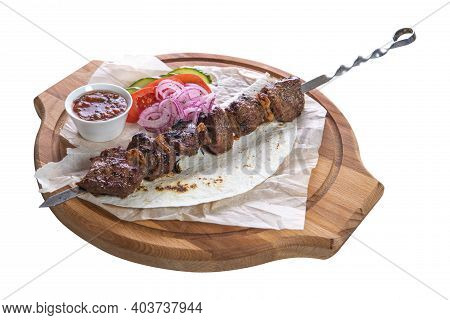 Pork Skewer On A Metal Skewer With Sauce, Sliced Cucumbers, Tomatoes And Onions  On A Wooden Tray On