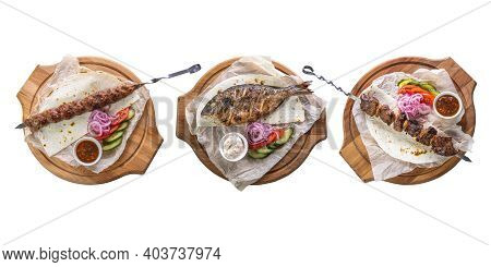 Three Dishes: Kebab, Grilled Dorado And Pork Kebab On A White Isolated Background. The Concept Of Re