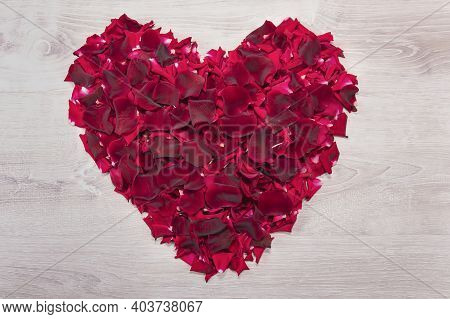 Postcard With A Big Heart Made Of Red Rose Petals On A White Vintage Wooden Table. Red Heart From Fl