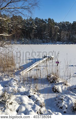 A Frozen Lake Surrounded By Tall Forest. Wooden Fishing Bridge Covered With Snow.