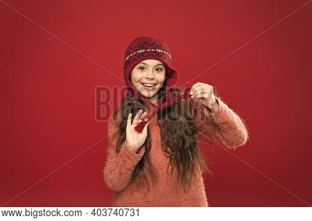 Stay Warm. Little Girl Winter Fashion Accessory. Small Child Long Hair Wear Hat Burgundy Background.