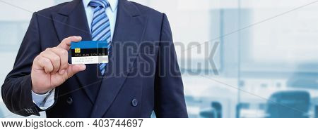 Cropped Image Of Businessman Holding Plastic Credit Card With Printed Flag Of Estonia. Background Bl