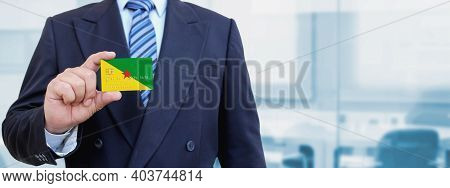 Cropped Image Of Businessman Holding Plastic Credit Card With Printed Flag Of French Guiana. Backgro