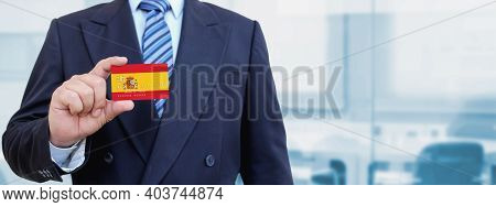 Cropped Image Of Businessman Holding Plastic Credit Card With Printed Flag Of Spain. Background Blur