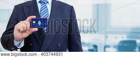 Cropped Image Of Businessman Holding Plastic Credit Card With Printed Flag Of Guam. Background Blurr