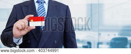 Cropped Image Of Businessman Holding Plastic Credit Card With Printed Flag Of Indonesia. Background