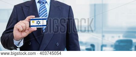 Cropped Image Of Businessman Holding Plastic Credit Card With Printed Flag Of Israel. Background Blu