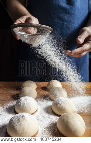 Bakers Hands Sprinkle Dough With Flour Using A Sieve