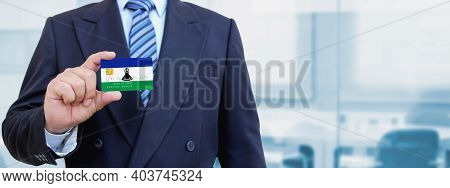 Cropped Image Of Businessman Holding Plastic Credit Card With Printed Flag Of Lesotho. Background Bl