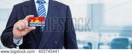 Cropped Image Of Businessman Holding Plastic Credit Card With Printed Flag Of Kiribati. Background B