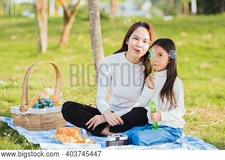 Happy Asian Mother And Little Girl Daughter Child Having Fun And Enjoying Outdoor Together Sitting O