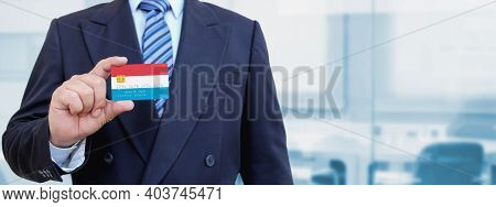 Cropped Image Of Businessman Holding Plastic Credit Card With Printed Flag Of Luxembourg. Background