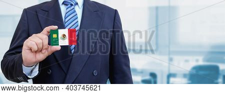 Cropped Image Of Businessman Holding Plastic Credit Card With Printed Flag Of Mexico. Background Blu