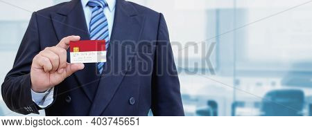 Cropped Image Of Businessman Holding Plastic Credit Card With Printed Flag Of Monaco. Background Blu