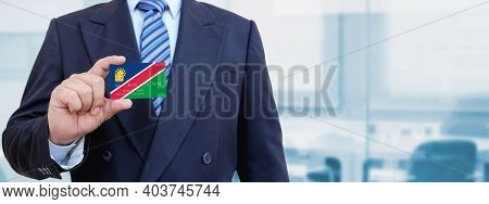 Cropped Image Of Businessman Holding Plastic Credit Card With Printed Flag Of Namibia. Background Bl