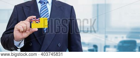Cropped Image Of Businessman Holding Plastic Credit Card With Printed Flag Of Niue. Background Blurr