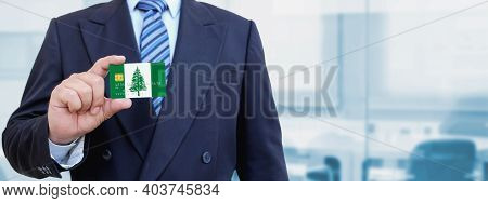 Cropped Image Of Businessman Holding Plastic Credit Card With Printed Flag Of Norfolk Island. Backgr